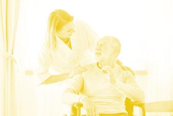 caregiver looking to the elder man smiling
