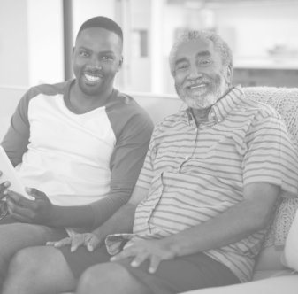 elder man and caregiver smiling in front of camera