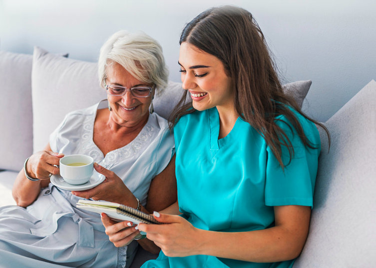 caregiver reading notes to an elder woman