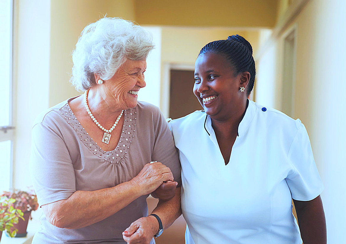 caregiver and elder woman smiling while walking